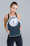 Portrait of happy fitness girl in sportwear with weigh scale Stock Image