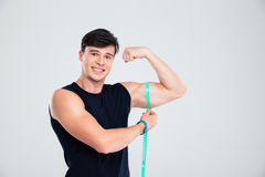 Portrait of a happy fitness man measuring his biceps Stock Photography