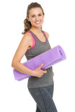 Portrait of happy fitness woman with fitness mat Royalty Free Stock Image
