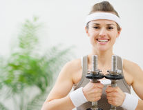 Portrait of happy fitness woman holding dumbbells Stock Photography