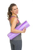 Portrait of happy fitness young woman with fitness mat Royalty Free Stock Image