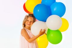 Happy little girl playing with colorful balloons. Portrait of happy five years old girl holding big bouquet of colorful balloons standing against blanked Stock Photo
