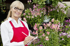Portrait of a happy florist taking notes in greenhouse Stock Photography