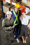 Portrait of Happy Foreman With Supervisors. High angle portrait of young foreman with supervisors smiling together at warehouse Royalty Free Stock Photography