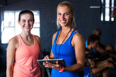 Portrait of happy friends with digital tablet in gym Stock Photography
