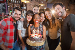 Portrait of happy friends holding birthday cake. In restaurant Stock Photos