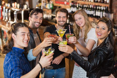 Portrait of happy friends holding drinks while standing in bar Royalty Free Stock Images