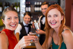 Portrait of happy friends holding a tequila shot in front of bar counter Royalty Free Stock Photos