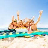 Happy kids laying on sandy beach and waving hands. Portrait of happy friends, laying on swimming equipment, waving hands and looking at camera stock photo