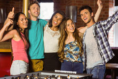 Portrait of happy friends playing table football Royalty Free Stock Photo