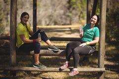 Portrait of happy friends relaxing on obstacle during obstacle course Royalty Free Stock Photos