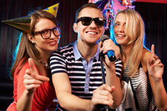 Karaoke party. Portrait of happy friends singing in microphone in the karaoke bar Royalty Free Stock Images