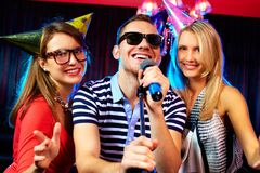 Karaoke party. Portrait of happy friends singing in microphone in the karaoke bar Stock Photos