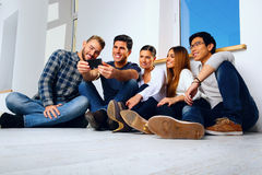 Portrait of a happy friends sitting on the floor. And looking at smartphone Stock Photos