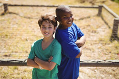 Portrait of happy friends standing with arms crossed during obstacle course. In boot camp stock photography