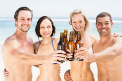 Portrait of happy friends toasting beer bottles on the beach. On a sunny day Royalty Free Stock Images