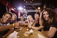 Portrait of happy friends toasting beer glasses while sitting at table Stock Image