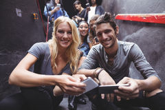 Portrait of happy friends using mobile phones on steps at nightclub Stock Photos
