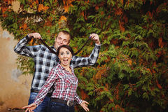 Portrait of happy fun young couple embracing in autumn park.  Royalty Free Stock Photos