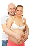 Portrait of happy future parents. Standing with hands on tummy together isolated on white background Stock Image