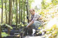 Portrait of happy gardener crouching while holding shovel at plant nursery Stock Photography