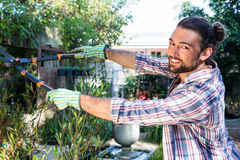 Portrait of happy gardener using clippers at garden royalty free stock photography