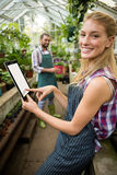 Portrait of happy gardener using digital tablet at greenhouse. Portrait of happy young female gardener using digital tablet at greenhouse Royalty Free Stock Photo