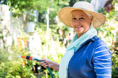 Portrait of happy gardener watering from hose at garden royalty free stock photos