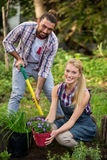 Portrait of happy gardeners with potted plant and shovel at garden Royalty Free Stock Photography