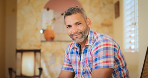 Portrait Happy Gay Man Looking At Camera Indoors. Portrait of homosexual adult man. Happy hispanic gay smiling at camera, sitting on sofa at home Royalty Free Stock Photography