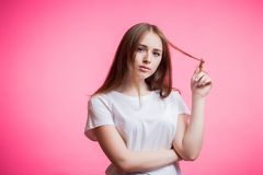 Portrait of happy ginger girl curling her hair with forefinger on pink background with copy space stock images
