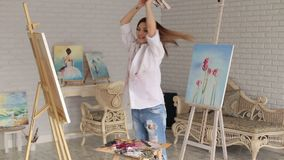 Portrait of happy girl artist in Studio to paint. A happy creative girl artist in a white shirt and jeans spinning around herself in a studio among many stock footage