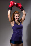 Portrait of happy girl in boxing gloves with raised hands. Royalty Free Stock Images