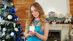 Portrait of happy girl with a candle in hand, Christmas fire, near the fireplace with burning fire, the girl makes a stock footage