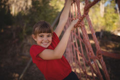 Portrait of happy girl climbing a net during obstacle course. In boot camp royalty free stock photo
