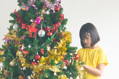 Portrait of happy girl decorating Christmas tree, filtered image Stock Photos