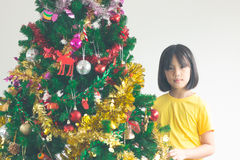 Portrait of happy girl decorating Christmas tree, filtered image Stock Photography