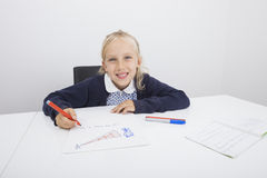 Portrait of happy girl drawing on paper at table Stock Image