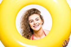 Portrait of a happy girl dressed in swimsuit looking through inflatable ring isolated over white background. Portrait of a happy girl dressed in swimsuit looking royalty free stock images