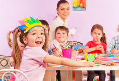Portrait of happy girl in early developing class. Portrait of happy little girl in early developing class in kindergarten with teacher and other children on royalty free stock image