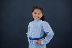 Portrait of happy girl with hand on hip. Standing against black backgrond Royalty Free Stock Images