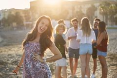 Happy girl with hand on hip standing on beach with friends. Portrait of happy girl with hand on hip standing on beach with friends Royalty Free Stock Photos