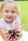 Portrait of a happy girl with hands full on bing cherries Stock Images
