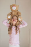 Portrait of happy girl holding stuffed toy over head Stock Photo