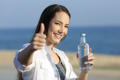 Girl holding a water bottle gesturing thumb up on the beach. Portrait of a happy girl holding a water bottle gesturing thumbs up on the beach Royalty Free Stock Photos