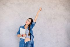 Portrait of happy girl with laptop pointing with left arm up. Portrait of happy girl, lady, female with laptop pointing with left arm up. Young woman in denim Stock Image