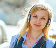 Portrait of happy girl listening music on city street Royalty Free Stock Image