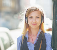 Portrait of happy girl listening music on city street Stock Photo