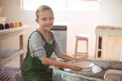 Portrait of happy girl making pot Stock Photo