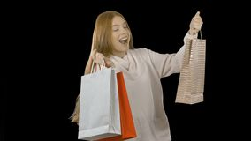Portrait of a happy girl with paper bags after buying a Christmas sale at discount prices Alpha matte. 4k stock footage
